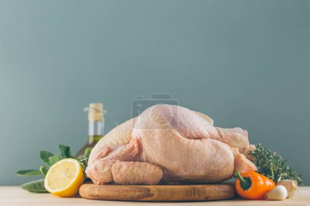 Photo for Raw chicken with ingredients for cooking and vegetables on kitchen table - Royalty Free Image