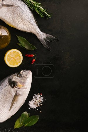 dorado fish and different spices on black table