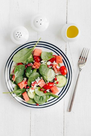 Photo pour Plaque avec mesclun et légumes et garnie de graines de Grenade et de fromage - image libre de droit