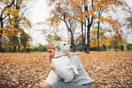 Photo pour Une véritable amitié, chien et propriétaire étreindre dans le parc - image libre de droit
