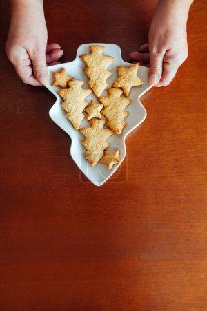 Photo pour Gros plan de femme tenant un bol décoré avec un biscuits de Noël - image libre de droit