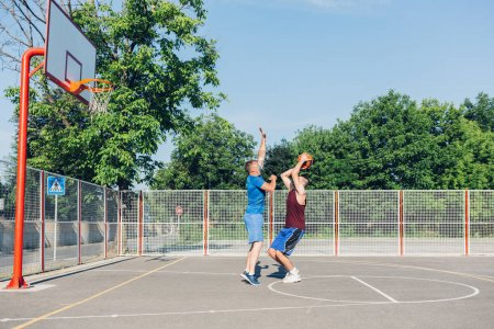 sporty men playing basketball