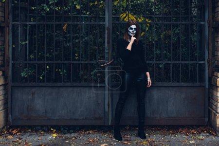 Foto de Longitud total de mujer en traje de esqueleto de pie junto a la puerta de hierro - Imagen libre de derechos