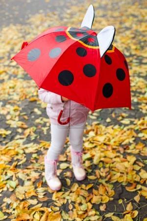 Preschool girl playing on autumn street