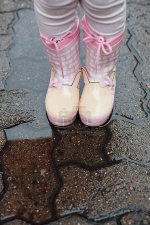 Girl standing in puddle