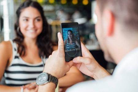man taking photo of beautiful young woman on smartphone sitting at table in cafe
