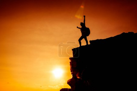 Sporty woman climbing on the cliff. Success and go...