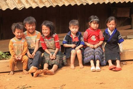 children sitting on wooden beam