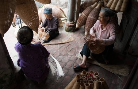 Photo for Three Vietnamese women making fish traps - Royalty Free Image