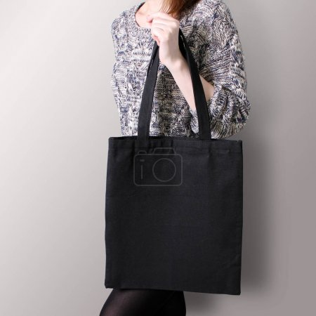 Mock-up. Girl is holding black cotton tote bag.