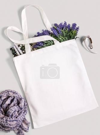 Photo pour Coton blanc blanc eco sac fourre-tout avec fleurs de lavande, magazine, montres et écharpe. Conception maquette. - image libre de droit