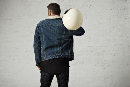 Photo pour Spine view of biker wears shearling denim jacket and black blank henley shirt, détient un casque de moto vintage beige, isolé au centre du mur de briques blanches - image libre de droit