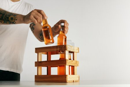 man's hands putting bottles into crate