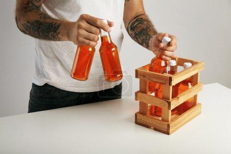 Tattooed man taking out bottles