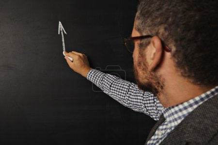 teacher starting to draw graph on blackboard