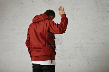 Photo pour Un jeune homme attrayant dans goodbye vagues veste rouge tiré de l'arrière fond de mur blanc - image libre de droit