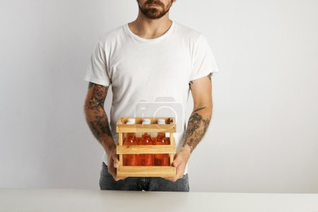 tattooed man holding crate with beer drinks