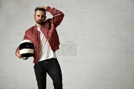 Photo for Tired young motorbiker in red bomber jacket, black jeans and white t-shirt adjusting his hairstyle and holding his white helmet - Royalty Free Image