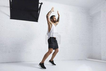 Photo pour Athlète tatoué et musclé faisant des sauts isolés sur un mur de briques blanches à côté de la barre de traction noire, regardant du côté droit - image libre de droit