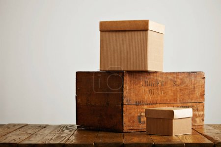 Photo pour Sans étiquette de boîtes en carton avec couvercles présentés à côté d'une caisse de vin vieux brune dans un studio avec des murs blancs - image libre de droit