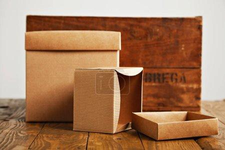 Photo pour Nouvelles boîtes en carton sans étiquette sur une table en bois brune rustique à côté d'une caisse de vin rétro isolée sur blanc - image libre de droit