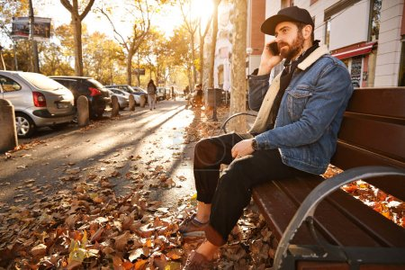 Photo for Attractive young man with a beard dressed in denim jacket, black trucker hat and black trousers sitting on a wooden bench in an autumn city street talking on the phone - Royalty Free Image