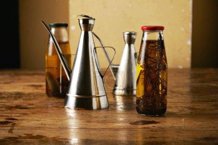 Photo pour Présentation de deux bouteilles en verre avec de l'huile d'olive épicée artisanale faite maison avec du romarin et des poivrons et deux béquilles métalliques brillantes sur une table brune rugueuse . - image libre de droit