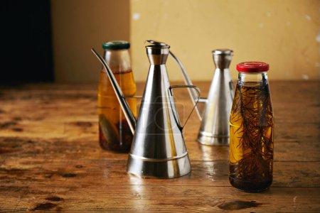 Photo pour Deux bouteilles d'huile d'olive épicée maison artisanale avec romarin et poivrons et deux béquilles métalliques brillantes sur une table brune rugueuse - image libre de droit