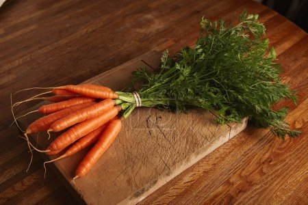 Photo for A bunch of fresh carrots on a weathered old cutting board with deep cuts on a beautiful wooden brown table - Royalty Free Image