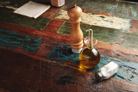 Photo for Wooden pepper grinder next to small glass dispencer with virgin extra olive oil inside stands near lying vitage jar with white sea salt, all isolated on distressed wooden table, top view - Royalty Free Image