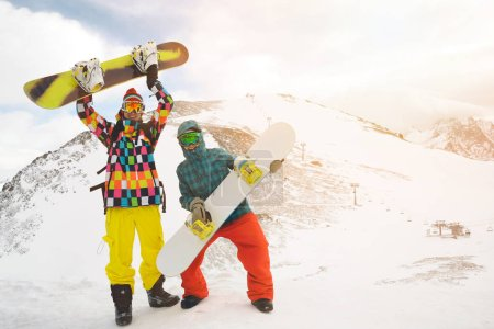 Snowboarding friends in mountains at