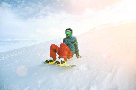 Девочка учится на сноуборде в горах