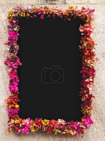 Flower framed around chalkboard on stone wall