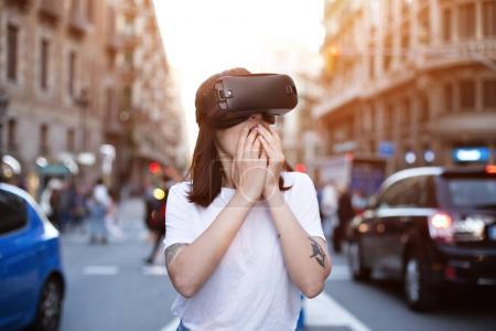 Photo pour Attrayant femme hipster est surpris par ce qu'elle voit à l'intérieur du casque futuriste vr - image libre de droit