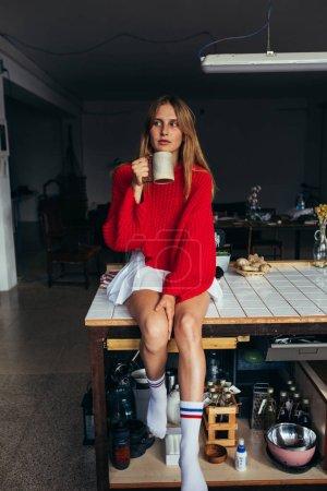 Photo pour Femme tendance en rouge surdimensionné tricot pull fait main se trouve sur le dessus du comptoir de cuisine dans la cuisine industrielle à la mode, beau design, boissons café - image libre de droit