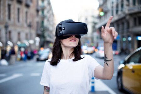 Photo pour Belle jeune femme cherche à comprendre si ce qu'elle voit à travers les lunettes virtuels est réel ou juste une projection, elle des gestes et des points sur des choses avec son bras tatoué - image libre de droit