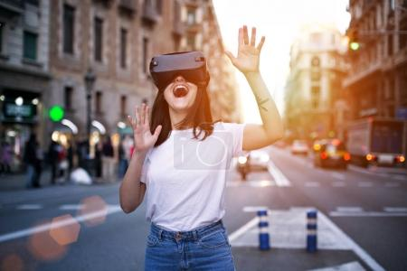 Photo for Young brunette is amused by her first encounter with futurist virtual reality glasses which alter the busy world around her - Royalty Free Image