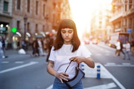 Photo pour Petite fille mignonne se dresse au milieu de la rue sur un soir d'été ensoleillée d'apprendre à porter des lunettes de réalité virtuelle technologie futuriste - image libre de droit