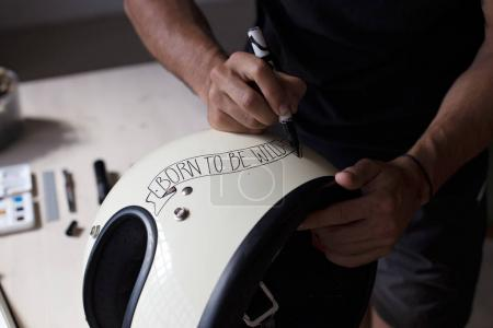 Close up designer customizing retro helmet