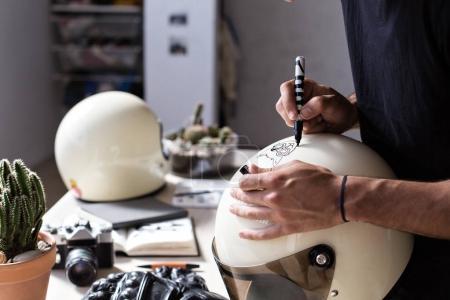 Close up designer customizing retro helmet