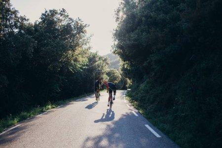Photo pour Deux cyclistes roulent sur une route vide à la campagne - image libre de droit