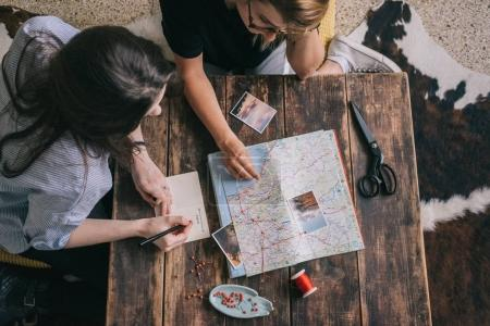 Photo for Two young cute girls explore paper map of Europe for new routes for summer trip. Students get inspired with photos of nature, write notes in notebook and planning their journey on dark wooden table - Royalty Free Image