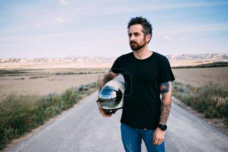 bearded Man holding vintage helmet