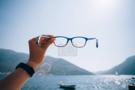 POV woman hold prescription glasses