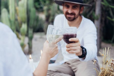 Couple clinks glasses on chic picnic