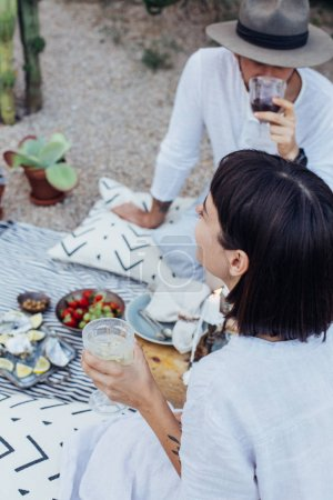 Hipster couple drinks wine on picnic