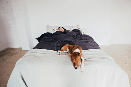 Woman and dog sleep in bed