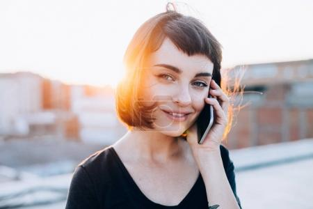 woman with short hair talking on smartphone
