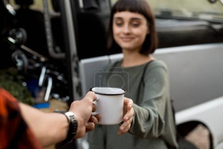pretty woman recieving metal mug