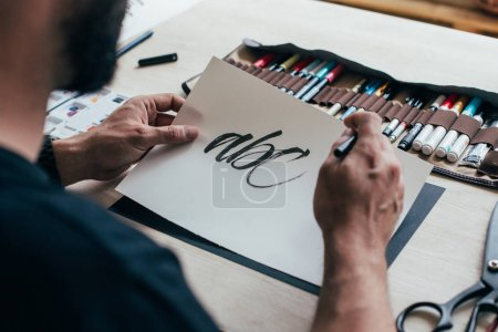 Photo for Man learning calligraphy lettering handwriting on drawing paper at table with pencil case - Royalty Free Image
